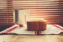 Bröd och breadmakertine vid fönstret Arkivfoton