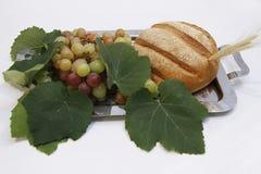 Bröd och druvor med sidor på magasinet på katolsk mass royaltyfria foton