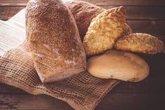Bröd och rullar på en träbakgrund Fotografering för Bildbyråer