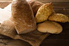 Bröd och rullar på en träbakgrund Arkivbilder