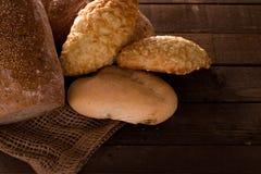 Bröd och rullar på en träbakgrund Royaltyfria Bilder
