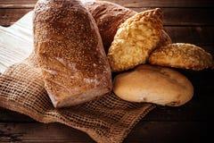 Bröd och rullar på en träbakgrund Arkivfoton
