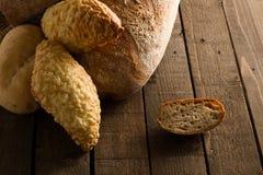 Bröd och rullar på en träbakgrund Royaltyfri Fotografi
