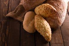 Bröd och rullar på en träbakgrund Arkivfoto