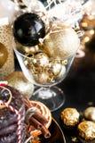 Bröd och sötsaker för julkortxmas ljust rödbrun, kakor på den svarta plattan, guld- bollar och konfettier med kanel, anis royaltyfria bilder