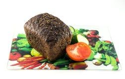 Bröd och tomat på en skärbräda Fotografering för Bildbyråer