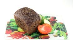 Bröd och tomat på en skärbräda Royaltyfri Foto