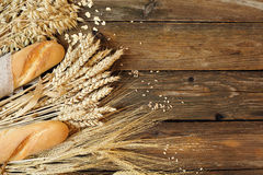 Bröd och tre typer av sädesslag - vete, råg och havre på ett trä fotografering för bildbyråer