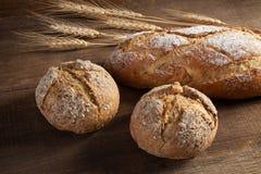 Bröd- och veteöron på träbakgrund Royaltyfri Foto
