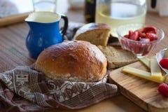 Bröd, ost och röd frukt med den blåa kannan Royaltyfria Bilder