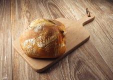 Bröd på träskärbräda Arkivbild