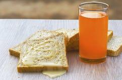 Bröd sötat förtätat mjölkar, och orange fruktsaft arkivfoton
