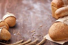 Bröd släntrar lantligt val av råg, sodavatten, bloomerbröd, med spannmålsmagasinet och oated rullar och öron av vete Arkivbilder