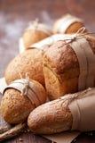 Bröd släntrar lantligt val av råg, sodavatten, bloomerbröd, med spannmålsmagasinet och oated rullar och öron av vete Royaltyfria Foton
