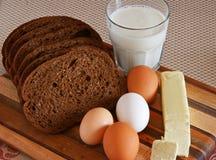 Bröd smör, ägg, mjölkar på en skärbräda Royaltyfri Foto
