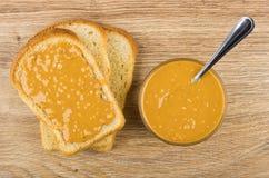 Bröd, smörgås med jordnötsmör, bunke och tesked på tabellen Royaltyfria Foton
