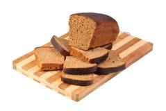 Bröd som skivas på skärbräda Arkivfoton