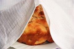 Bröd som täckas med en vit servett arkivbilder