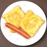 Bröd som två täckas med ägget och korven Arkivfoton