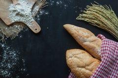 Bröd, vete och mjöl på den svarta svart tavlan, bageribakgrund Fotografering för Bildbyråer