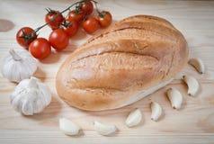 Bröd vitlök, körsbärsröda tomater Fotografering för Bildbyråer