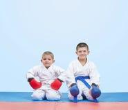 Bröder karate sompojkar sitter i karate, poserar på matsna Royaltyfri Foto