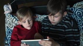 Bröder med minnestavladatoren i mörkt rum  arkivfilmer