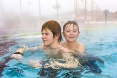 Bröder simmar i det utvändiga området av en thermic pöl i W fotografering för bildbyråer