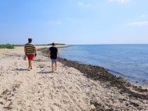 Bröder som går med kal fot i sanden längs kusten royaltyfria bilder