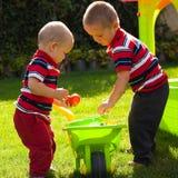 bröder som little arbeta i trädgården Arkivbilder