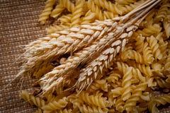 Brödgrova spikar och pasta på grov tygbakgrund arkivbilder