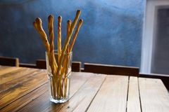 Brödpinnar med sesamfrö i en glass kopp är på tabellen i ett kafé Arkivfoto