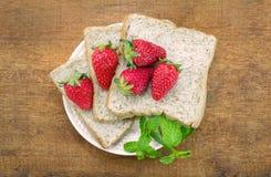 Brödskiva och jordgubbe för helt vete Royaltyfri Foto