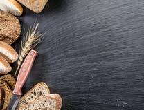Brödskivor, ett vete och en kniv på den svarta stenen Royaltyfria Foton