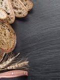 Brödskivor på det svarta stenskrivbordet Arkivbilder