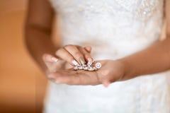 Bröllopörhängen på en brud- hand, bruds morgon- och smyckentillbehör och garneringbegrepp, selektiv fokus royaltyfri fotografi
