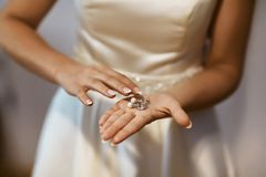 Bröllopörhängen på en brud- hand, tillbehör för morgon och för smycken för brud` s och garneringbegrepp royaltyfri foto