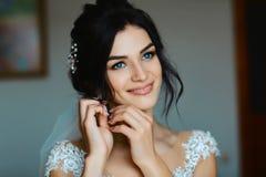 Bröllopörhängen på en kvinnlig hand, tar hon örhängena, brudavgifterna, morgonbruden, den vita klänningen, kläderörhängen royaltyfri fotografi