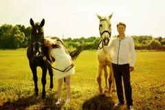 Bröllop av lyckliga near hästar för ovanliga par Royaltyfri Bild
