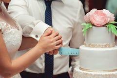 bröllop för brudceremoniblomma bruden och brudgummen gör deras första fall tillsammans, klippte bröllopstårtan Royaltyfri Foto