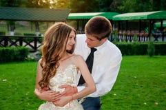 bröllop för tappning för klädpardag lyckligt Lyckliga par in i parkera Det lyckliga ung flickainnehav hänger lös på en vitbakgrun Royaltyfri Bild
