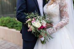 bröllop Flickan i en vit klänning och en grabb i en dräkt rymmer en härlig bukett av vit och rosa färgblommor och grönska wed royaltyfri bild
