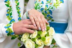Bröllop händer för brud` s med vigselringar på en bröllopbukett royaltyfri foto