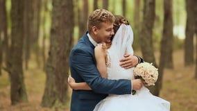 bröllop Lyckliga par i en skog i den nya luften Elegant brudgum bak brud I händerna av en härlig bukett av arkivfilmer