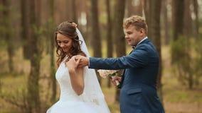 bröllop Lyckliga par i en skog i den nya luften Elegant brudgum bak brud I händerna av en härlig bukett av stock video