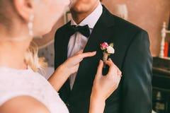 bröllop Närbildbrud` s räcker att klämma fast boutonniere till smokingen för brudgum` s Varmt tonar Arkivfoto