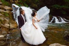 Bröllop par nära den härliga storslagna vattenfallet i berg Vind som fladdrar ett långt, skyler Landskap av kullar och berg royaltyfria bilder