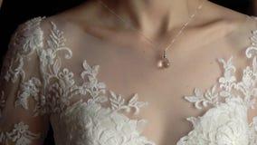 bröllop smycken Bruden i en vit klänning som sätter på en halsband runt om hennes hals arkivfilmer