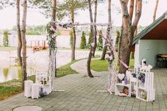 Bröllopbegreppet för öppen luft av tappningbröllopbågen som dekoreras med blommor och omges av träaskar och Royaltyfri Foto