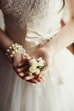 Bröllopboutonniere i händerna av bruden Arkivbilder